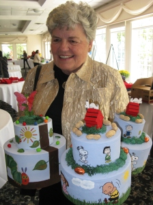 Auxiliary member Marge Skarbeck shows off some of the cake centerpieces she decorated.