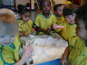 Toddlers at the Day Nursery Clarian center play with fresh snow in their water table.