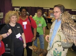 Day Nursery State Center Director Deanna Saylor (left) and Clarian Center Director Jesse McCloud (in red) talk to Jungle John and his feathered friend Whoo-sier about Silly Safari visits during the IAEYC conference last year.