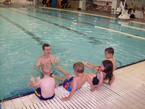 Preschoolers learn how to kick from their water safety instructor