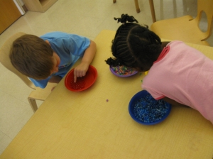 Preschoolers at the Day Nursery at Ft. Harrison sort out red and blue beads during Celebrate America week.  Activities like bead sorting strengthen fine motor skills in children which lays the foundation for writing in elementary school.