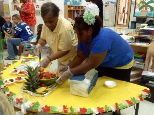 Teachers spread out fresh fruit for a snack