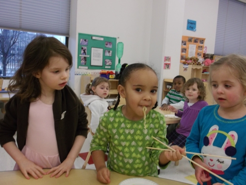 Day Nursery children trying to eat with chopsticks