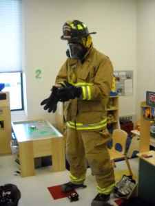 Firefighter showing children his gear
