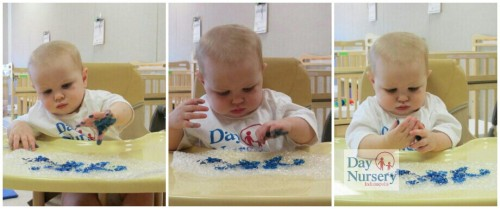infant in high chair painting on bubble wrap