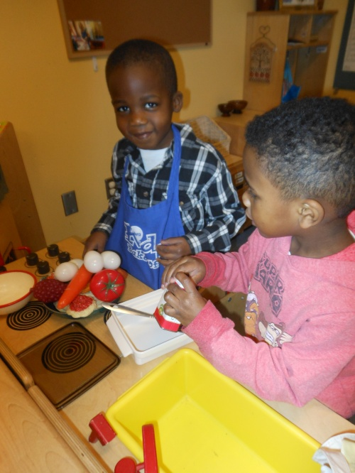 Day Nursery Indianapolis students cut pretend vegetables in the dramatic play area