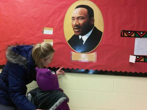 A parent and child at Day Nursery Hendricks County  stop to discuss the display honoring Dr. Martin Luther King, Jr.