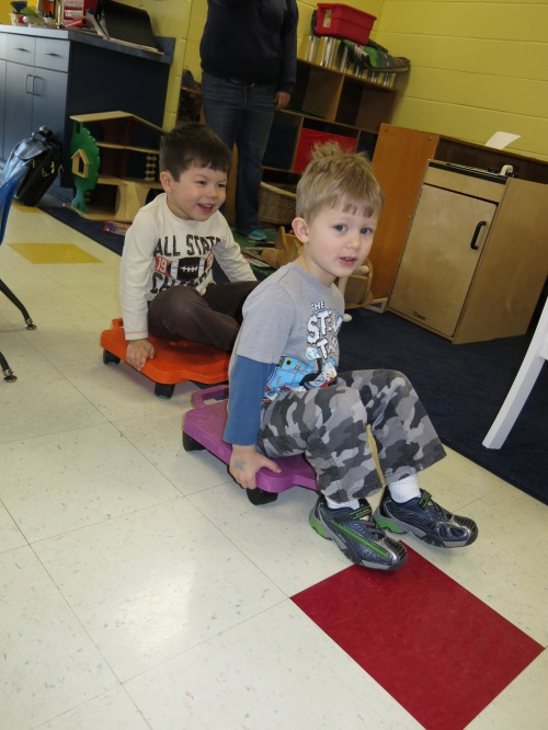 Day Nursery preschoolers on classroom scooters