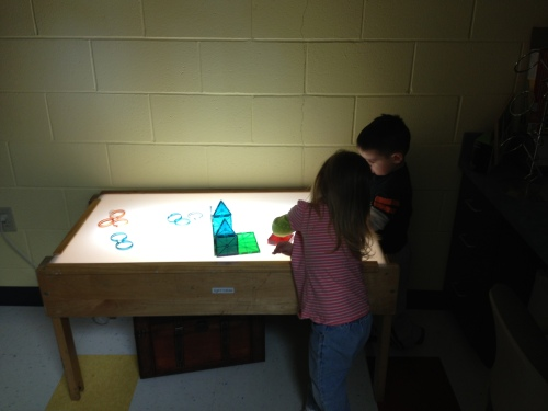 Day Nursery preschoolers experimenting with a light table