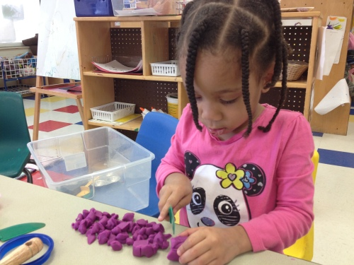 Day Nursery Northwest Indianapolis student pretending to cook with food made out of playdough