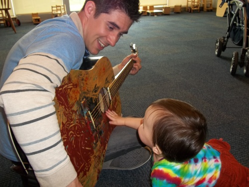 Day Nursery teacher plays a guitar for students