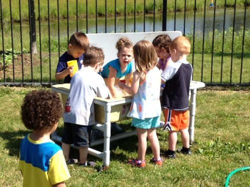 Day Nursery preschoolers playing in outdoor water table