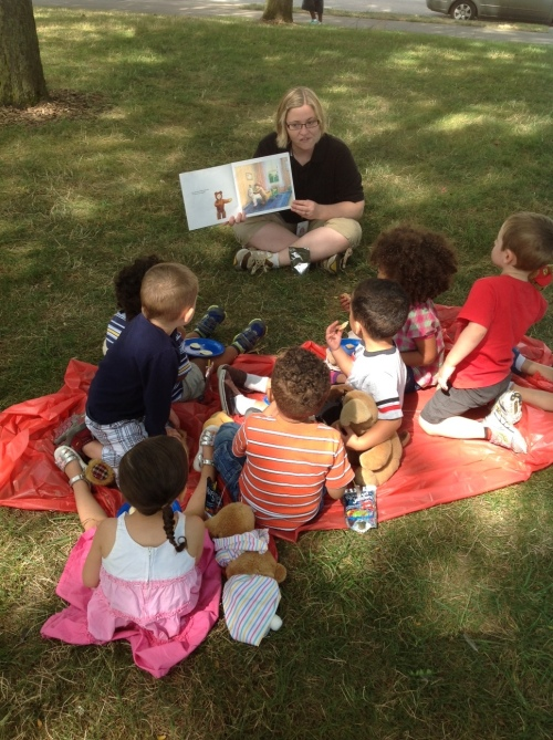 Day Nursery Indianapolis Federal Center students listening to story while in the park for teddy bear picnic