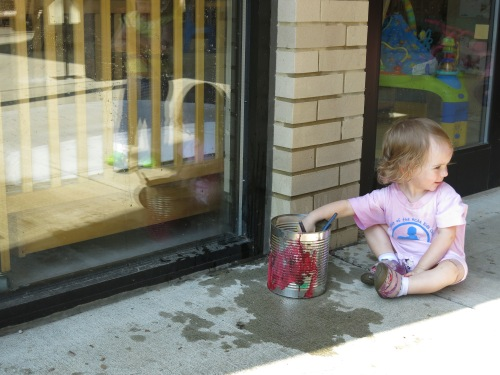 Toddlers painting windows with water