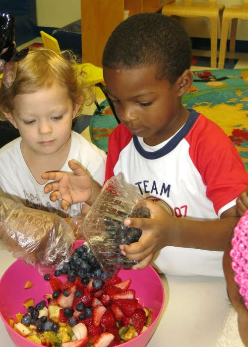 Day Nursery preschoolers adding blueberries to the fruit bowl
