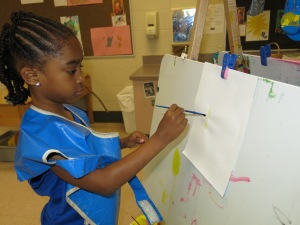 Day Nursery student painting on an easel