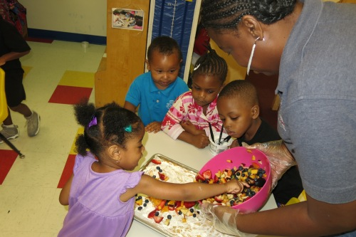 Day Nursery students spread the mixed fruit across the cream cheese base of their fruit pizza