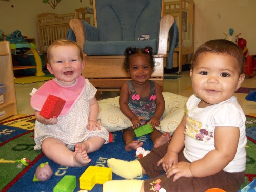 Three Day Nursery infants sitting on floor playing with foam blocks.